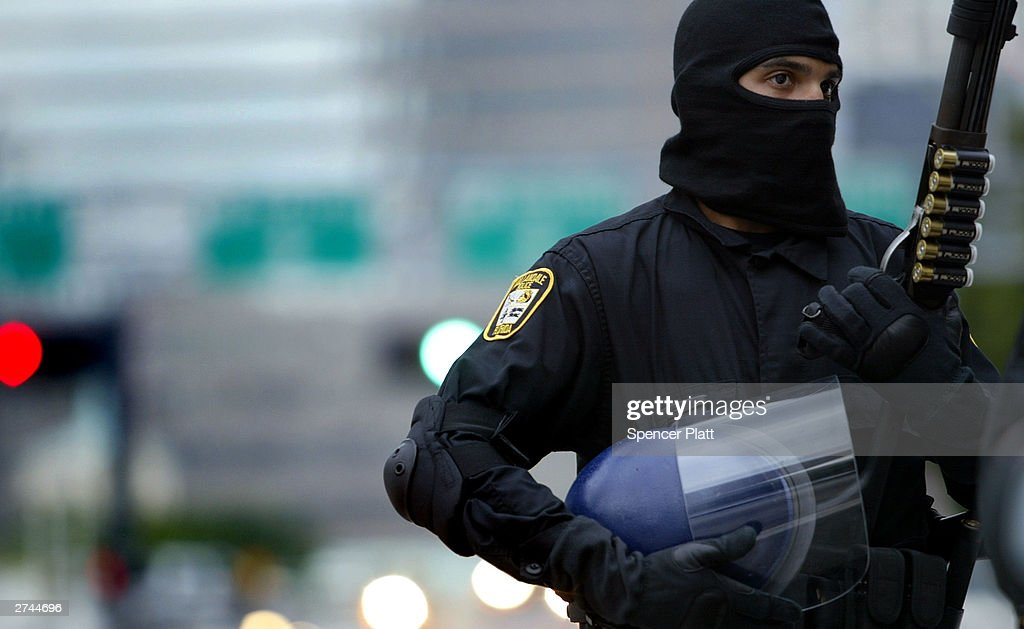 A Miami policeman stands guard in riot gear November 19, 2003 in Miami on the third day of the summit to create a Free Trade Area of the Americas (FTAA) being held in Miami, Florida. Due to expected protests from anarchists, labor groups and globalization foes, much of the city of Miami is in a police lockdown, with thousands of businesses closed and a steel barricade circling the summit area. Large demonstrations are planned for Thursday.