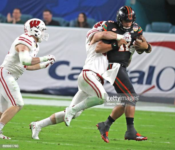 Miami quarterback Malik Rosier is tackled by Wisconsin's Andrew Van Ginkel in the second quarter during the Capital One Orange Bowl at Hard Rock...