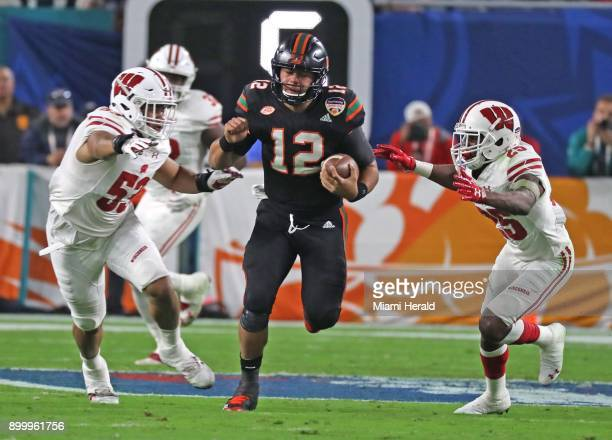 Miami quarterback Malik Rosier runs into Wisconsin defenders TJ Edwards and Derrick Tindrl in the first quarter during the Capital One Orange Bowl at...