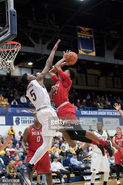 Miami RedHawks G Michael Weathers is fouled by Kent State Golden Flashes F Danny Pippen during the first half of the men's college basketball game...