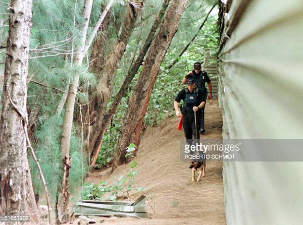 Miami Springs police K9 unit searches 17 July a canal area near the home of an unidentified medical doctor who was found murdered inside his home in...