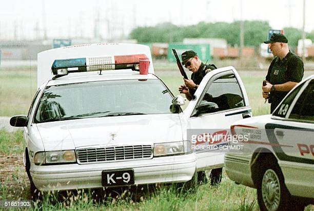 Miami Springs Sargent Randy Walker , a member of a K-9 police unit, handles a shotgun as he joins others in a search 17 July for serial killer Andrew...
