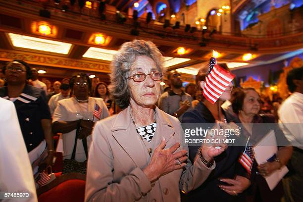 An immigrant holds a US flag as she and others pay respect to the US colors during a naturalization ceremony in Miami Florida 28 April 2006 Some 250...