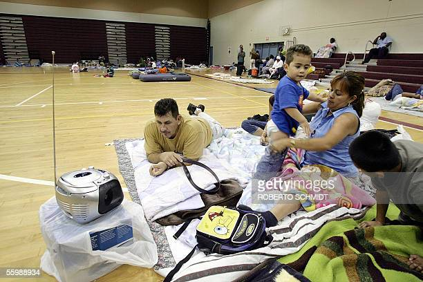 Faustino Trejo watches a hurricane storm update on a portable TV as his wife Esmeralda finishes changing the diapers of their 3yearold son Justino at...