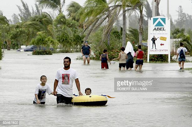 Mark Balencourt uses a raft to ferry his sons Alec and Jose through flooded streets due to Hurricane Katrina 26 August 2005 in Miami, FL. Storm-weary...
