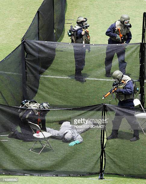 Members of a Federal Bureau of Investigations Special Weapons and Tactics team wearing biological and chemical protective gear clear a make believe...