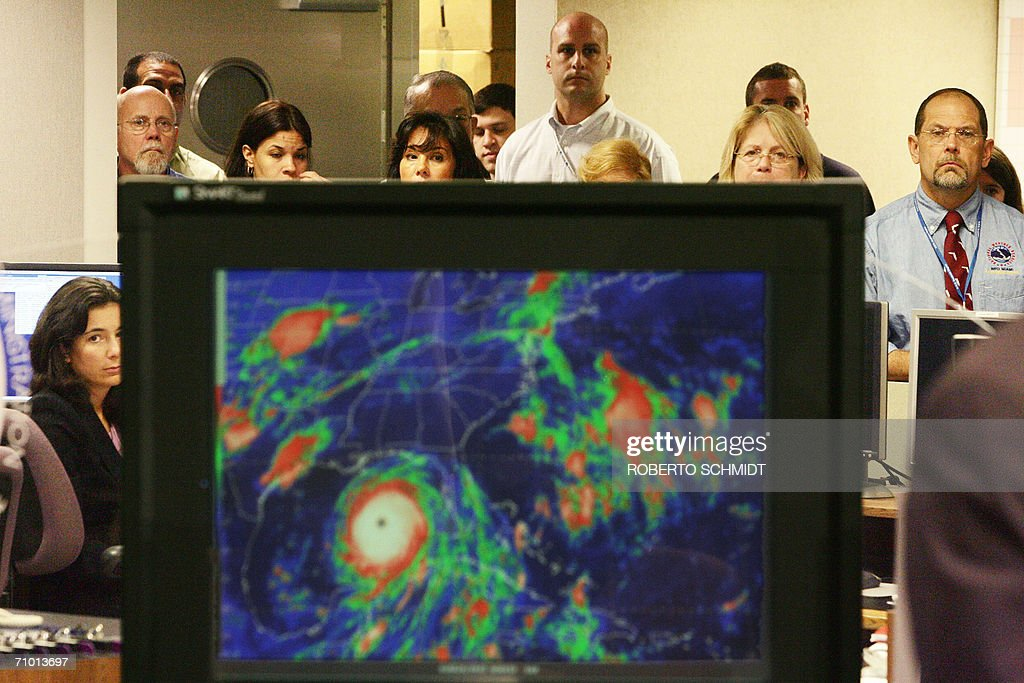 Staff members of the National Hurricane Center listen to a press conference by the center's director as they watch from behind a computer screen showing satellite graphics of hurricane Katrina in 2005 at the National Hurricane Center in Miami 22 May 2006. National Oceanic and Atmospheric Administration (NOAA) Director Max Mayfield said that 'for the 2006 north Atlantic hurricane season, NOAA is predicting 13 to 16 named storms, with eight to ten becoming hurricanes, of which four to six could become 'major' hurricanes of Category 3 strength or higher.' Experts also urged residents to prepare for potentially devastating storms. AFP PHOTO/Roberto SCHMIDT