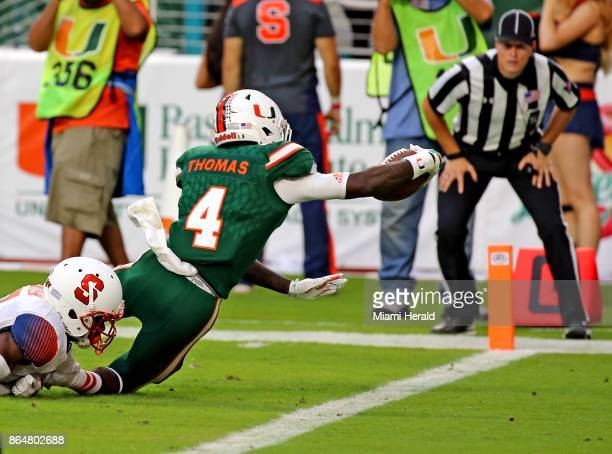 Miami wide receiver Jeff Thomas finishes a 48yard thirdquarter touchdown reception as Syracuse's Devin Butler brings him down at Hard Rock Stadium in...