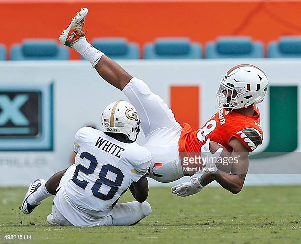 Miami wide receiver Lawrence Cager makes a second-quarter reception as Georgia Tech defensive back D.J. White defends at Sun Life Stadium in Miami on...