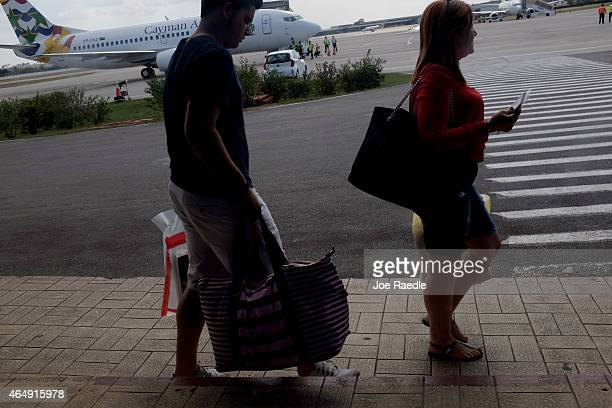 Miamibound passengers walk to a bus as they prepare to board a charter plane at José Martí International Airport on March 1 2015 in Havana Cuba The...