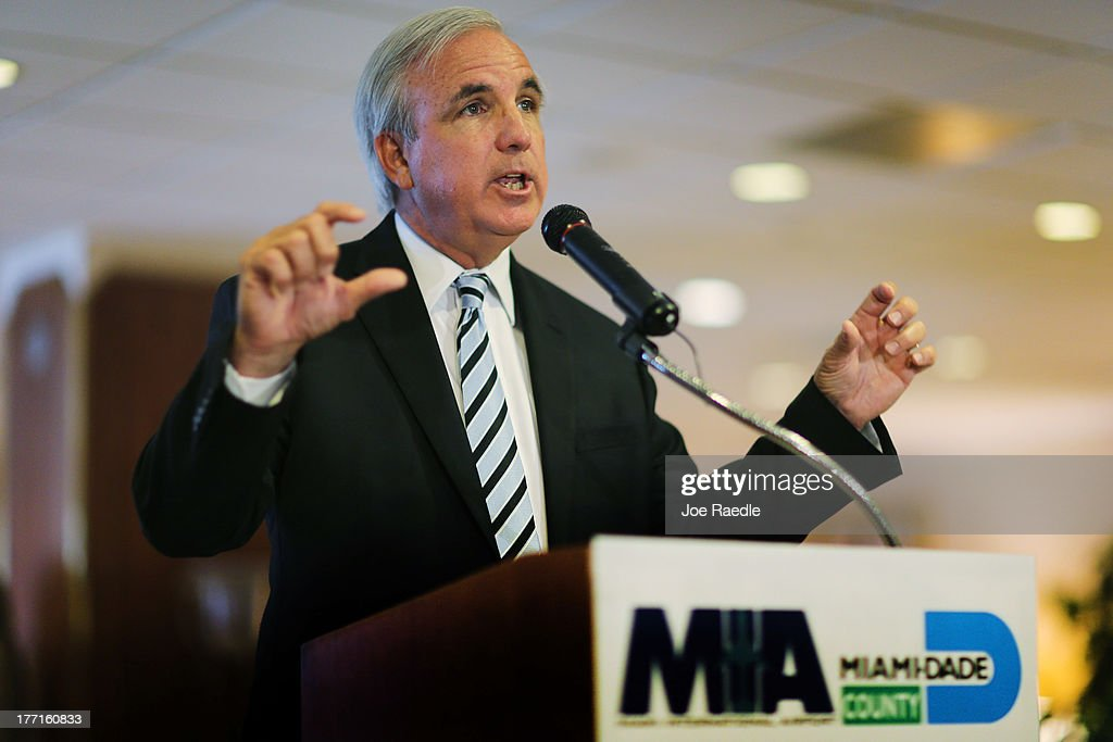 Miami-Dade County Mayor Carlos A. Gimenez speaks to the media regarding the U.S. Justice Department and state attorneys general suit against the American Airlines and US Airways merger on August 21, 2013 in Miami, Florida. The Mayor and Miami International Airport Aviation Director Emilio T. González addressed the letter they sent Attorney General Eric H. Holder, Jr. in which they stated their concerns with the review of the merger due to the damage it will do to the local economy if the merger isn't allowed to go through.