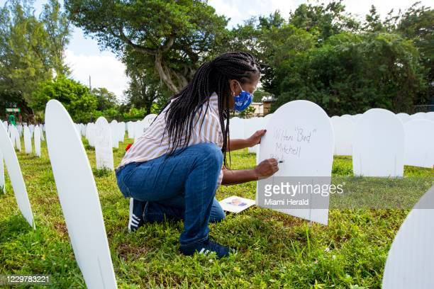 Miami-Dade County resident Joanna Moore creates a tombstone for her late mothers first cousin who recently passed from COVID-19 after an event to...