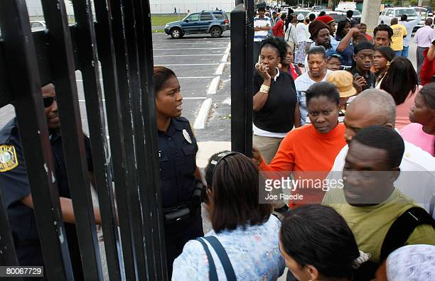 MiamiDade County schools police open a gate to let parents in ten at a time to find their children at Miami Edison Senior High School after a melee...