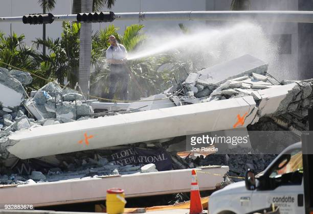 MiamiDade Fire Rescue Department official uses a hose to spray water to keep down the dust at the scene of a pedestrian bridge that collapsed a few...