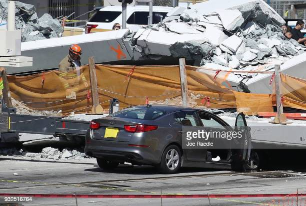 MiamiDade Fire Rescue Department personel and other rescue units work at the scene where a pedestrian bridge collapsed a few days after it was built...