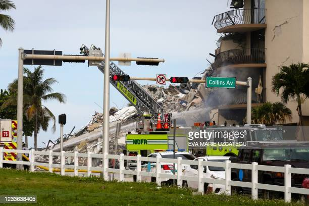 Miami-Dade firefighter sprays water to the debris from a partially collapsed building in Surfside north of Miami Beach, on June 24, 2021. - A...
