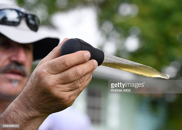 MiamiDade mosquito control worker Carlos Vargas looks for the Aedes aegypti mosquito larvae at a home in Miami Florida on June 08 2016 Of the forty...