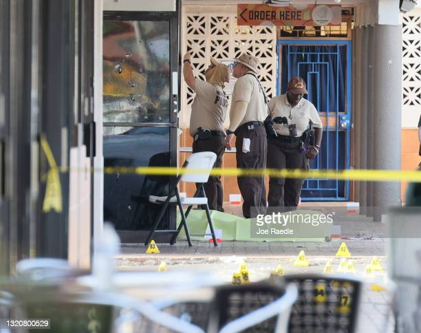 Miami-Dade police investigate near shell case evidence markers on the ground and a door with what appear to be bullet holes where a mass shooting...