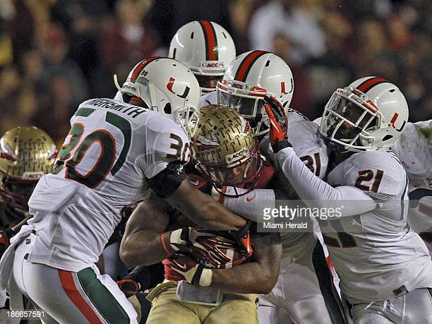 Miami's defense smoothers Florida State's Karlos Williams in the first quarter at Doak Campbell Stadium in Tallahassee Florida on Saturday November 2...