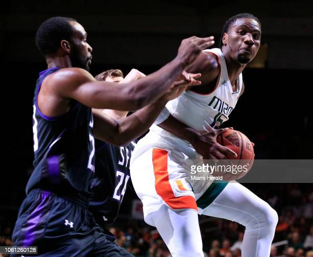 Miami's Ebuka Izundu looks to pass around Stephen F. Austin's Samuli Nieminen and Nathan Bain in the first half at Watsco Center in Coral Gables,...