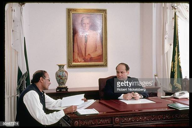 PM Mian Nawaz Sharif conferring w hovering secytype aide persuing papers at his desk