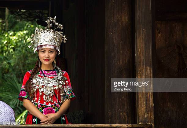 Miao female dressed in traditional wedding costume standS in a attic The Miao is one of the 55 official minority groups in China