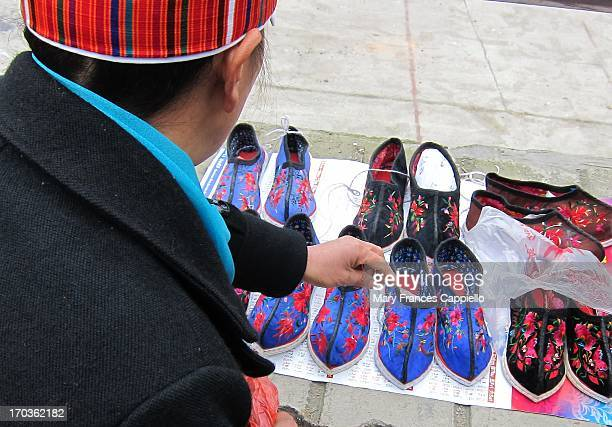 Miao minority woman sells handmade shoes at the weekly market in Shidong, Guizhou, February 2013. She did all the embroidery herself.