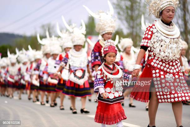 Miao people dressed up in traditional silver-decorated costumes parade to celebrate Zimei Jie at Taijiang County on April 28, 2018 in Qiandongnan,...