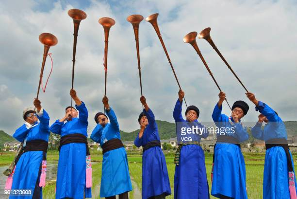 Miao people play the suona at a folk festival which falls on the eighth day of the fourth month in Chinese lunar calendar on May 22, 2018 in Anshun,...