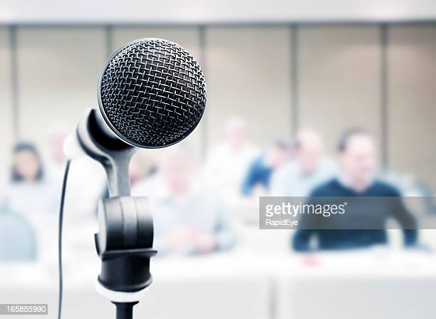 mic stands ready in front of blurred audience - microphone stand stock photos and pictures