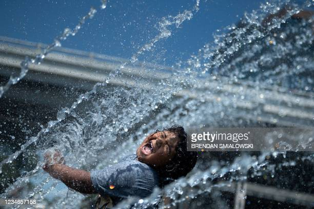 Micaela Montelara plays in the fountain at Georgetown Waterfront Park during a heatwave on August 13 in Washington, DC. - July was the hottest month...