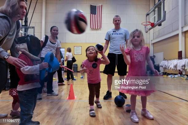 Micaela Perezous center Sterling and Ainsley Cates right Chantilly throw balls into a net with help from Alex Feige with Fit Kids at the Outdoors...