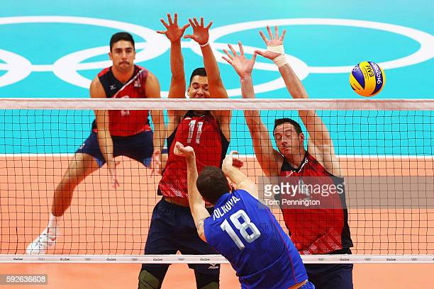 Micah Christenson of United States and David Lee of United States block the spike of Alexander Volkov of Russia during the Men's Bronze Medal Match...