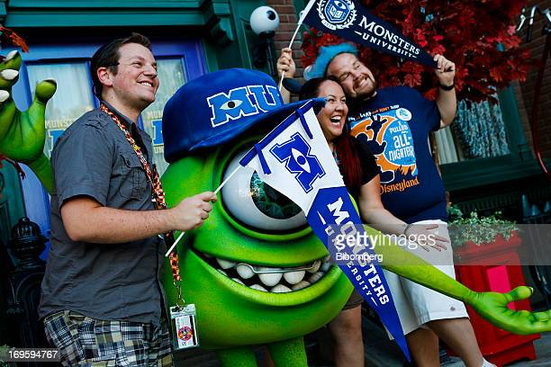 Micah Hardt Erin Kiser and Matt Eickhoff pose for photos with the Walt Disney Co Monsters University character Mike Wazowski outside the Monsters...