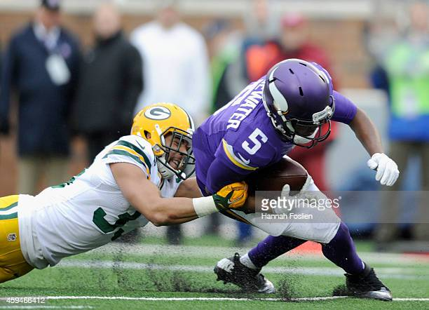 Micah Hyde of the Green Bay Packers tackles Teddy Bridgewater of the Minnesota Vikings during the fourth quarter of the game on November 23 2014 at...