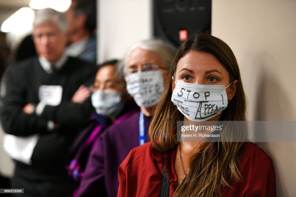DENVER, CO - OCTOBER 30 - Micah Parkin, right, of 350 Colorado and Colorado Rising, and Liz Fuhr, second from right, of Sisters of St. Francis, wear masks to show their opposition to COGCC board members during a public comment session on October 30, 2017 in Denver, Colorado. The Colorado Oil and Gas Conservation Commission (COGCC) will be deciding whether to approve the location of 84 wells Extraction Oil & Gas Inc wants to drill in Broomfield. The proposed project has generated a lot of controversy with both Broomfield and Adams county residents upset about the particular location of the wells and how they might affect neighbors and water supplies. Dozens of residents turned out to voice their opposition to the project. The mission statement for the COGCC says that they are charged with fostering the responsible development of Colorado's oil and gas natural resources in a manner consistent with the protection of public health, safety, and welfare, including the environment and wildlife resources. Their agency seeks to serve, solicit participation from, and maintain working relationships with all those having an interest in Colorado's oil and gas natural resources.