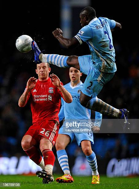 Micah Richards of Manchester City beats Charlie Adam of Liverpool to the ball during the Carling Cup Semi Final First Leg match between Manchester...