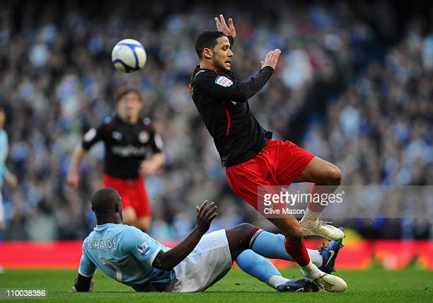 Micah Richards of Manchester City tackles Jobi McAnuff of Reading during the FA Cup sponsored by EOn Sixth Round match between Manchester City and...