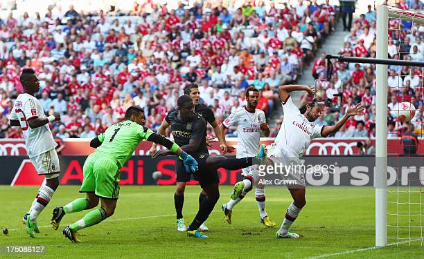 Micah Richards of Manchester scores his team's second goal against goalkeeper Marco Amelia and Cristian Zaccardo of Milan during the Audi Cup match...