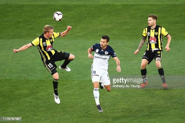 Michał Kopczynski of the Phoenix competes for the ball against Kosta Barbarouses of the Victory during the ALeague match between the Wellington...