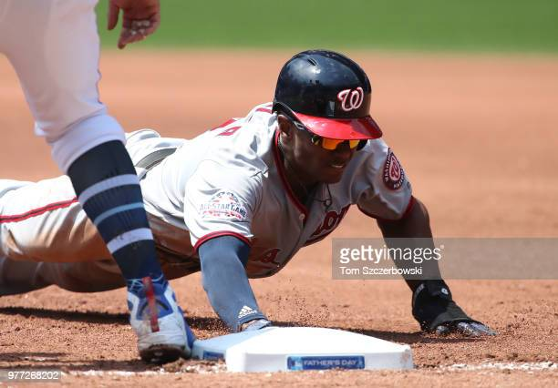 Michael A Taylor of the Washington Nationals dives back safely to first base on a pickoff attempt in the fourth inning during MLB game action against...