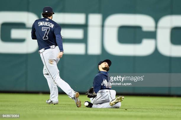 Michael A Taylor of the Washington Nationals hit drops in for a double between Dansby Swanson and Ender Inciarte of the Atlanta Braves during a...