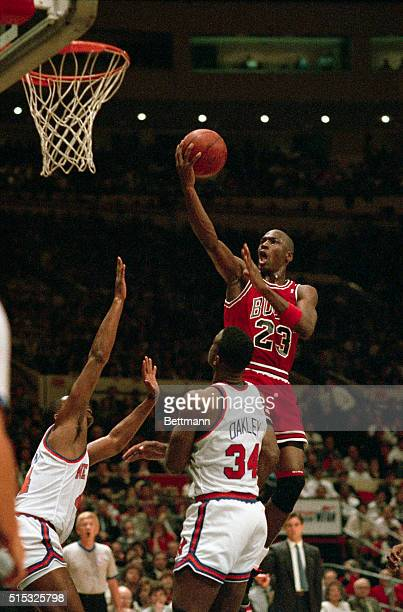 Michael Air Jordan soars over two New York Knicks Sidney Green and Charles Oakley as he drives for two points during their NBA Playoff Game here 5/16...