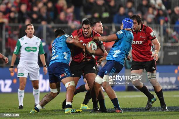 Michael Alaalatoa of the Crusaders is tackled by Akira Ioane of the Blues and Gerard CowleyTuioti of the Blues during the round 19 Super Rugby match...