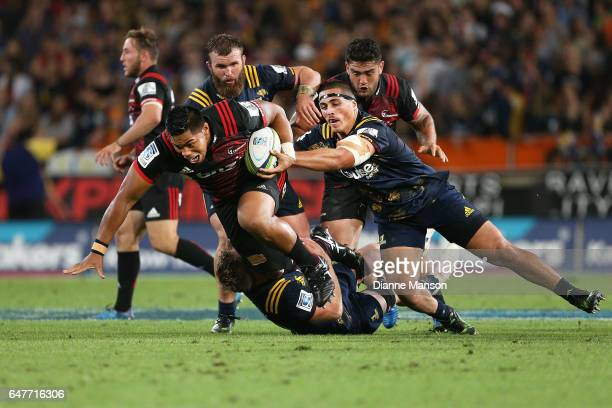 Michael Alaalatoa of the Crusaders tries to break the tackle of Daniel LienertBrown of the Highlanders during the round two Super Rugby match between...