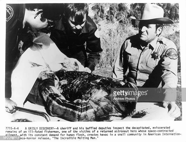 Michael Alldredge a sheriff inspects the decapitated remains of a fisherman in a scene from the film 'The Incredible Melting Man' 1977