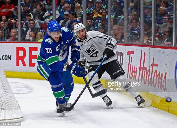 Michael Amadio of the Los Angeles Kings checks Brandon Sutter of the Vancouver Canucks during their NHL game at Rogers Arena October 9, 2019 in...