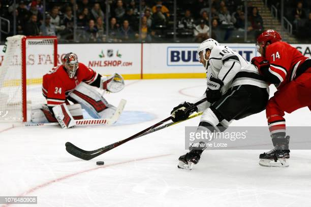 Michael Amadio of the Los Angeles Kings takes a shot on Petr Mrazek of the Carolina Hurricanes as Jaccob Slavin of the Carolina Hurricanes follows...