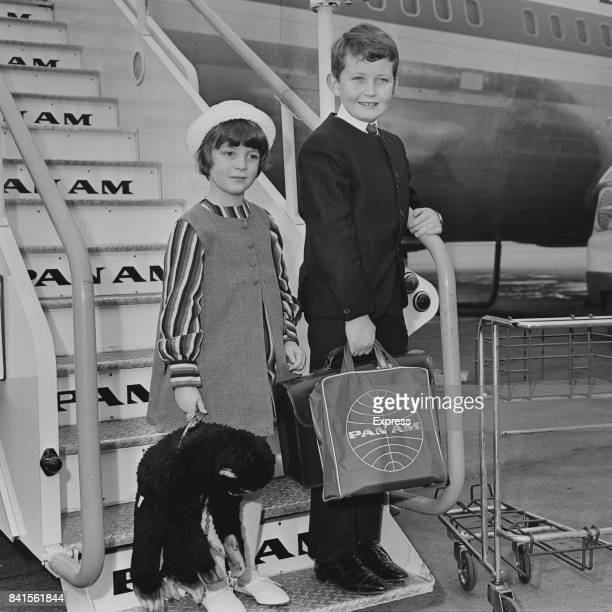 Michael and Sarah Sellers children of British actors Peter Sellers and Anne Howe stands on a Pan American World Airways boarding stairs while...