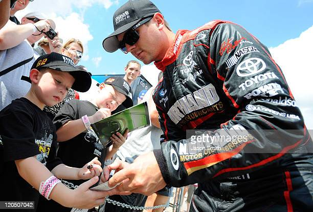 Michael Annett driver of the Northland Motor Oils Toyota signs autographs for a young fan during qualifying for the NASCAR Nationwide Series US...